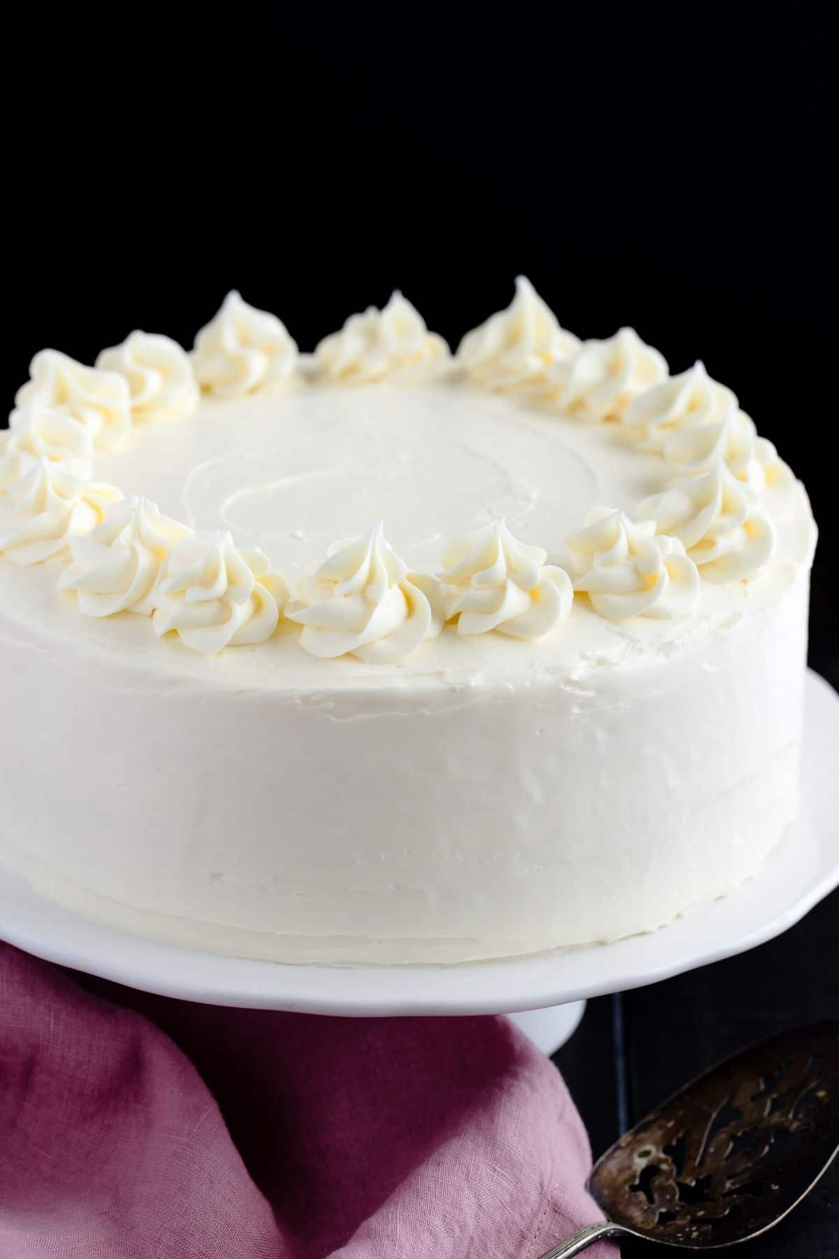 Los pasteles de vainilla caseros se colocan en un soporte de pastel blanco.