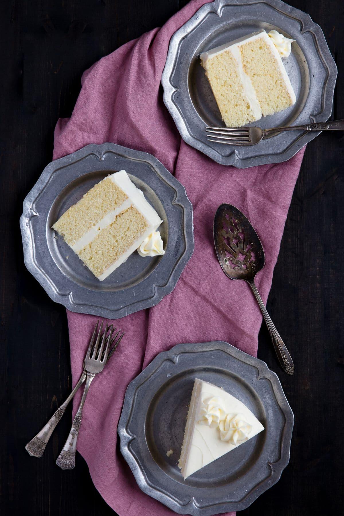 Tres platos de peltre cada uno con un trozo de tarta de vainilla.