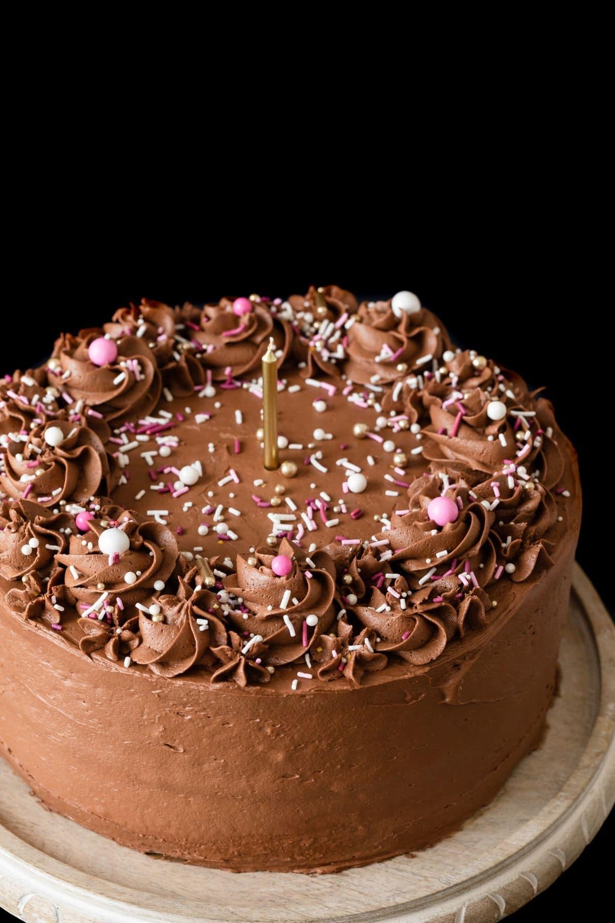 Vista en ángulo de tarta de cumpleaños casera con glaseado de chocolate y chispitas.