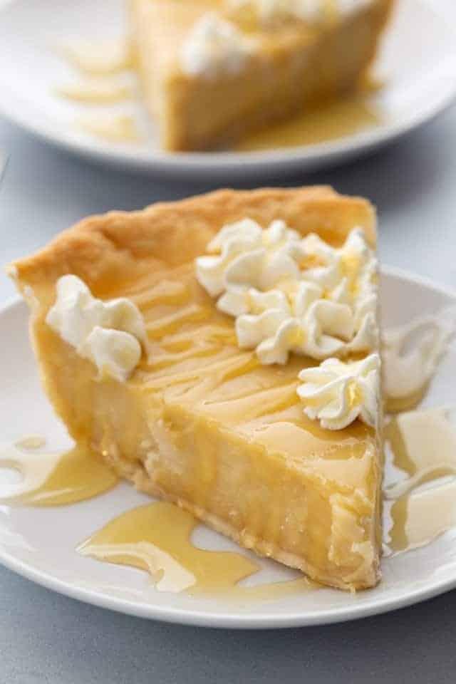 Vista lateral de un trozo de pastel de miel en un plato blanco.