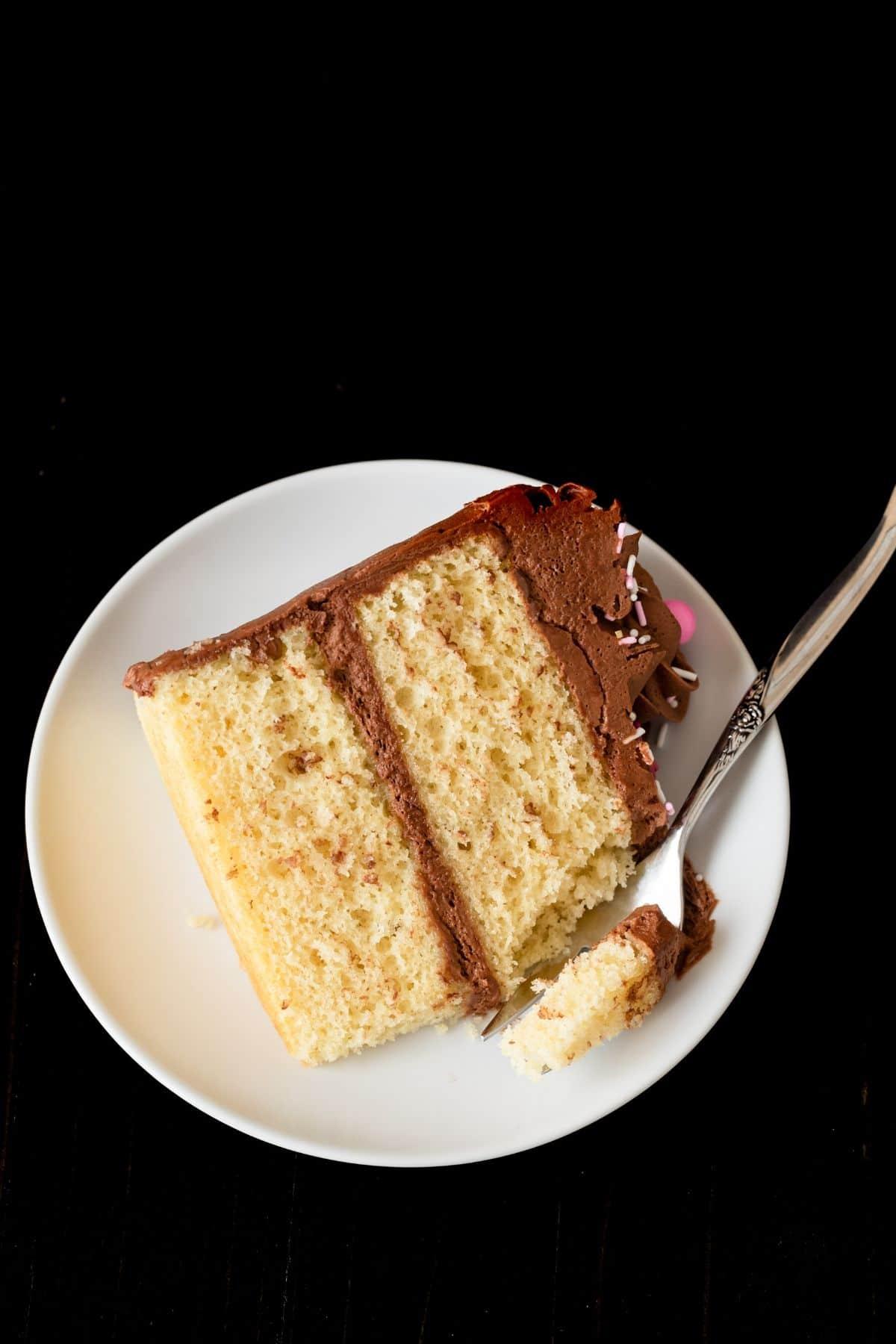 Muerde un trozo de pastel de cumpleaños en un plato blanco con un tenedor.
