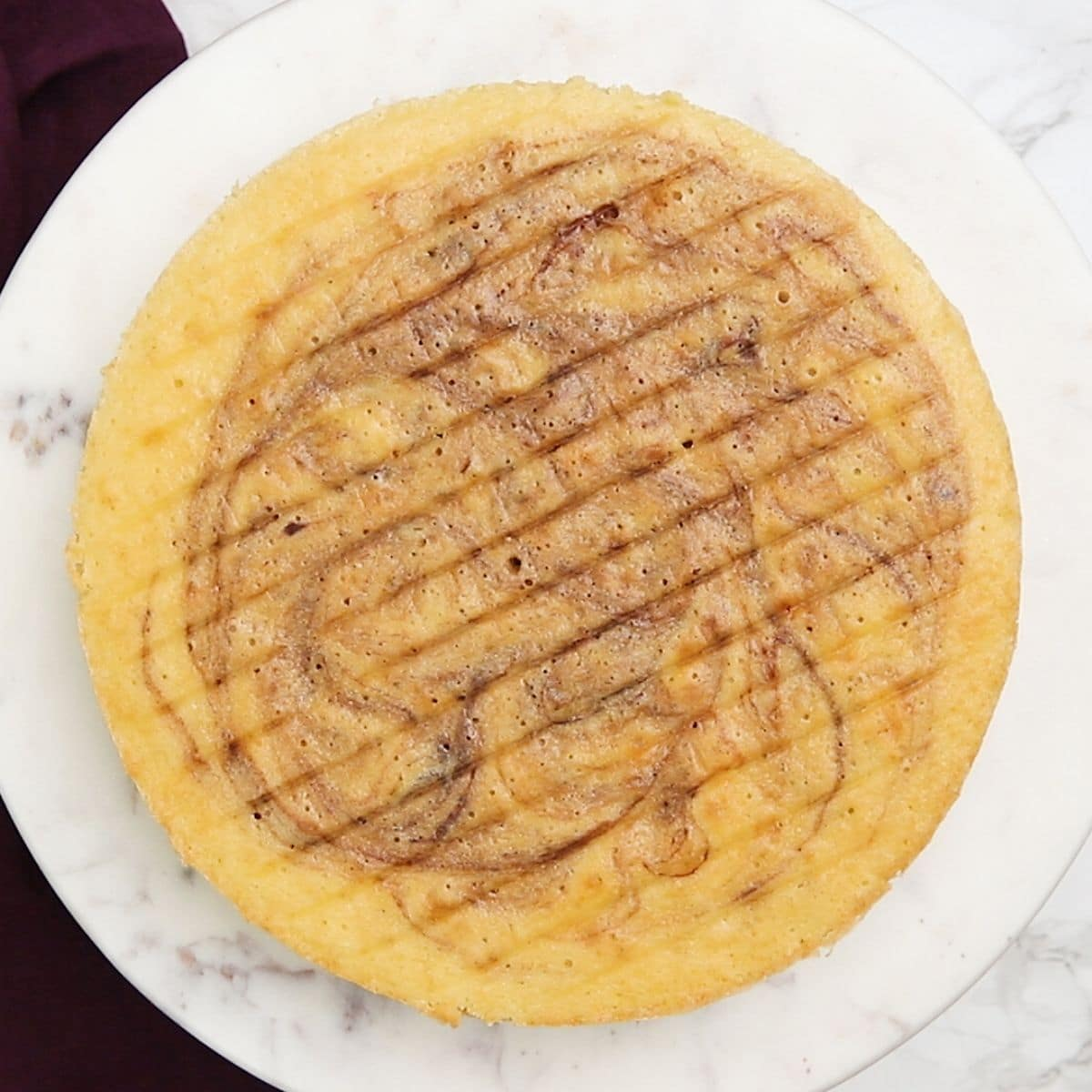 Capa de pastel de mármol horneado sobre un soporte para pasteles
